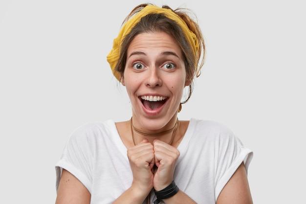 Bliska strzał radosnej kobiety rasy kaukaskiej, która trzyma rękę wciśniętą razem, uśmiecha się pozytywnie