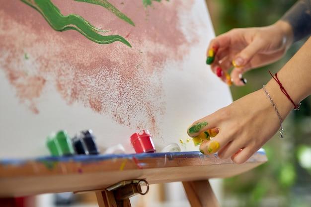 Bliska strzał rąk w farbie artystki tworzącej malarstwo abstrakcyjne w warsztacie studyjnym w domu