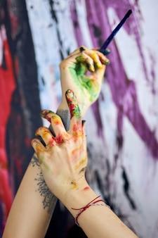 Bliska strzał rąk w kolorowe farby kobiecej malarki tworzącej malarstwo abstrakcyjne w warsztacie