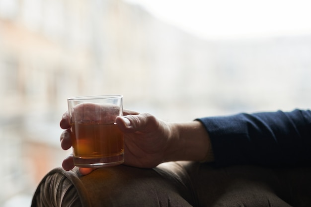 Bliska strzał ręki udanego biznesmena trzymającego szklankę szkockiej whisky z alkoholem