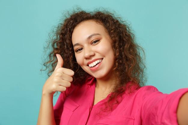 Bliska strzał selfie uśmiechnięta dziewczyna afryki w ubranie wyświetlono kciuk na białym tle na tle niebieskiej ściany turkus w studio. ludzie szczere emocje, koncepcja stylu życia. makieta miejsca na kopię.