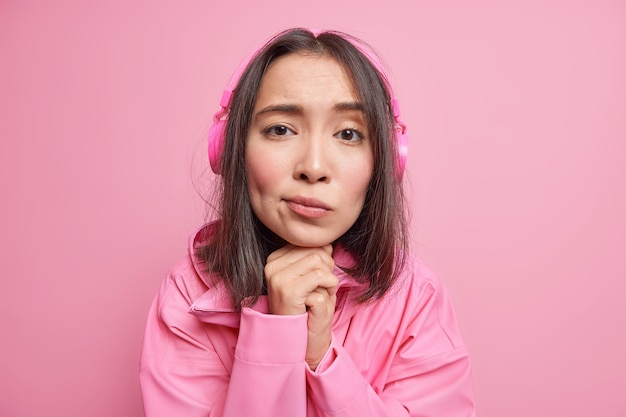 Bliska strzał smutna rozczarowana tysiącletnia dziewczyna trzyma ręce pod brodą z melancholijnym wyrazem twarzy słucha tekstów piosenek przez słuchawki ubrana w kurtkę na białym tle nad różową ścianą