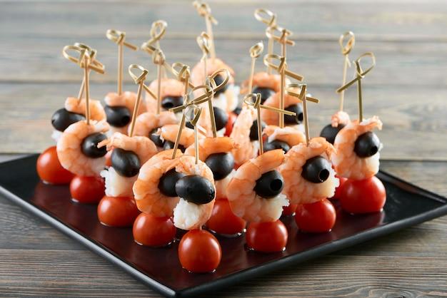 Bliska strzał świeże krewetki podawane z pomidorkami cherry i czarnymi oliwkami na drewnianym stole w luksusowej restauracji cafe przystawka owoce morza warzywa zdrowe odżywianie jedzenie.