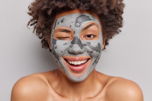 Bliska strzał szczęśliwa młoda afro amerykanka mruga oczami, uśmiecha się szeroko lubi procedury pielęgnacji skóry