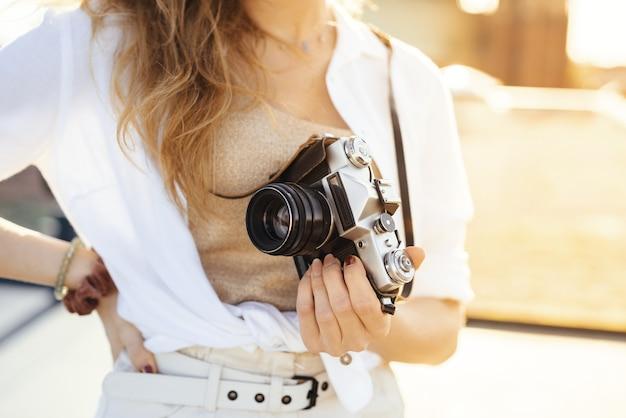 Bliska strzał szczęśliwej, modnie ubranej podróżniczki z aparatem przy słonecznej pogodzie