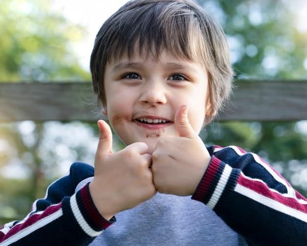 Bliska strzał szkolnego chłopca z brudną twarzą z lodami czekoladowymi, urocze dziecko uśmiecha się z bałaganem w ustach czekolady i pokazuje dwa palce, słodkie dziecko daje kciuk w górę na znak sukcesu