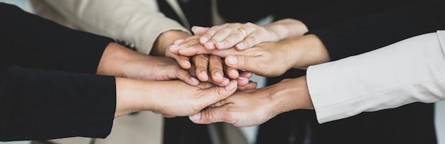 Bliska strzał trzymając się za ręce niezidentyfikowanej, nie do poznania, udanej grupy kobiet businesswoman razem w formalnym garniturze nosi zachęcać jako zaufanie do umowy o partnerstwie w pracy zespołowej.