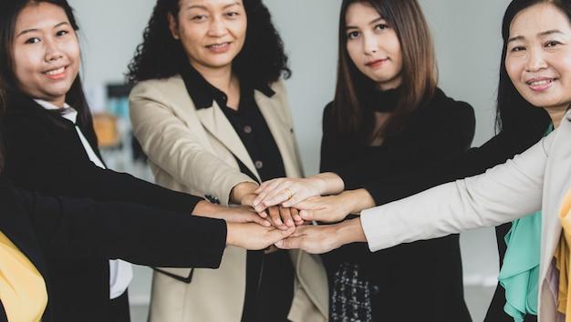 Bliska strzał trzymając się za ręce w średnim wieku udanej grupy koleżanek kobieta businesswoman stojącej uśmiechnięci razem w formalnym garniturze zachęcają do wzmocnienia zaangażowania partnerstwa.