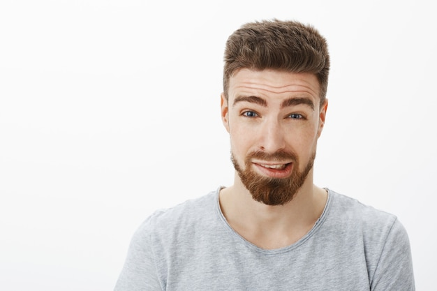 Bliska strzał winnego słodkiego chłopaka z brodą i brązową fryzurą, unosząc brwi, próbując przeprosić za popełnienie błędu, mówiąc przepraszam, czuję się niezręcznie i zdezorientowany na białej ścianie