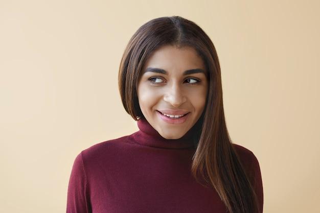 Bliska strzał wspaniałej młodej brunetki rasy mieszanej odwracającej wzrok z tajemniczym uśmiechem, jakby flirtując z kimś. pozytywna mimika, emocje, uczucia, reakcje i nastawienie człowieka