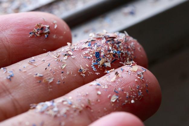 Bliska strzał z boku mikroplastików leżał na rękę ludzi. pojęcie zanieczyszczenia wody i globalnego ocieplenia. pomysł na zmiany klimatu.