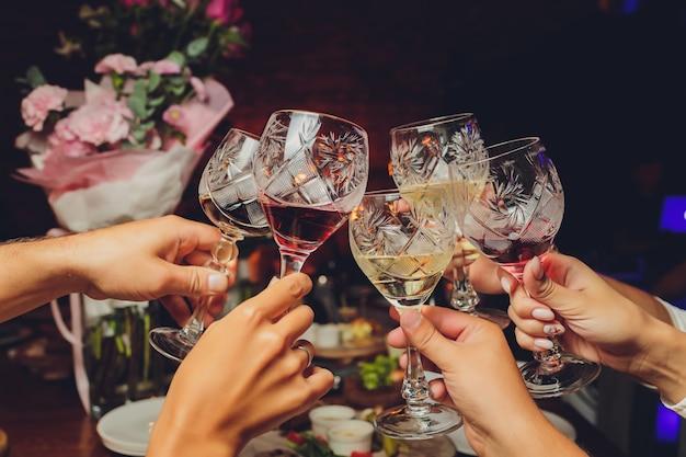Bliska strzał z grupą ludzi szczęk kieliszków z winem lub szampanem przed tło bokeh. ręce osób starszych.