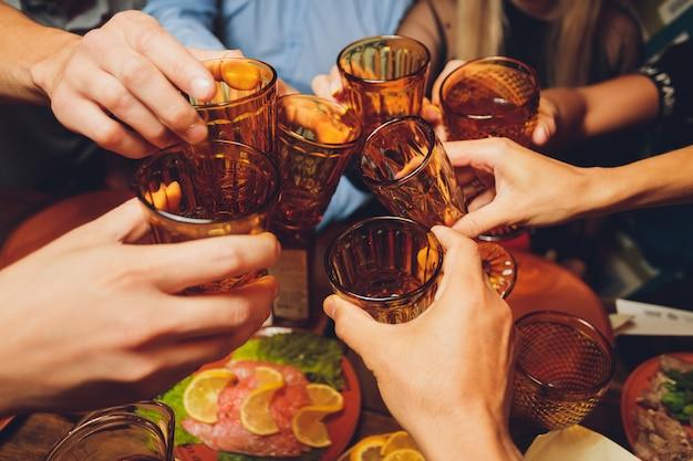 Bliska strzał z grupy ludzi szczęk kieliszków z winem lub szampanem