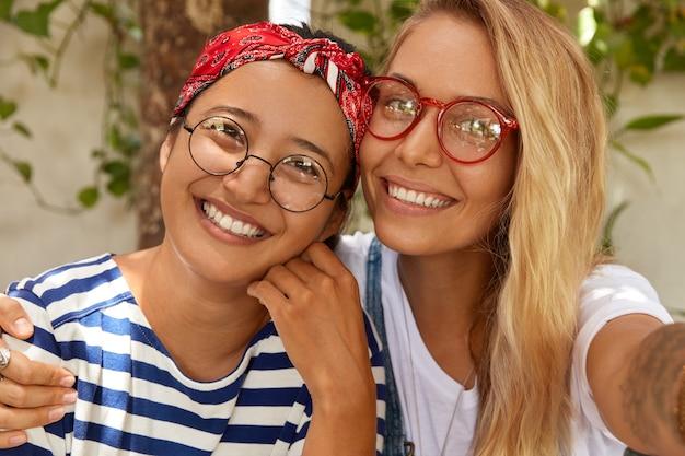 Bliska strzał z przyjemnie wyglądających dwóch wesołych kobiet rasy mieszanej uśmiechają się radośnie, obejmują się