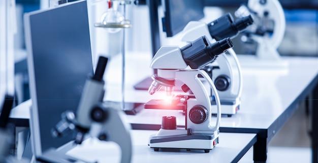 Bliska strzał z przyrządu mikroskopu naukowego wizjera z czerwonym światłem flary na soczewce i próbce szklanej płytki w rzędzie na biurku laboratoryjnym przy użyciu do monitorowania koronawirusa covid 19.
