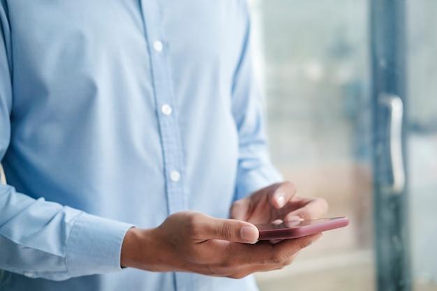 Bliska strzał z rąk mężczyzny trzymając telefon komórkowy podczas korzystania z bezprzewodowego szybkiego połączenia z internetem.