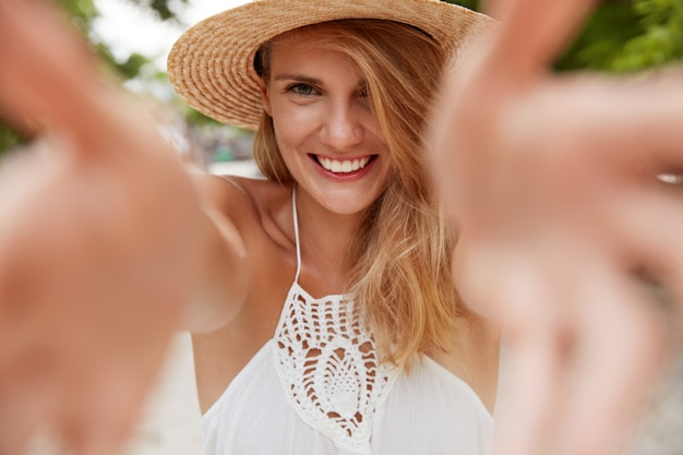 Bliska strzał zadowolonej, uśmiechniętej kobiety rozciąga ręce, by cię objąć, cieszy się dobrym letnim dniem na świeżym powietrzu, ubrana w modną sukienkę i kapelusz