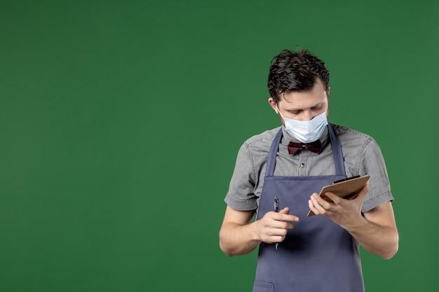 Bliska strzał zajętego męskiego kelnera w mundurze z maską medyczną i trzymając książkę zamówień na zielonym tle