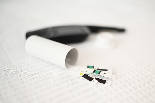Bliska strzał zestaw lancetu dla diabetyków z zapasowymi igłami, glukometr, paski, pudełko zapasowych pasków, wstrzykiwacz. glukometr glukometru, test glukozy we krwi