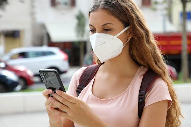 Bliska studentka z wiadomościami z maską ochronną z inteligentnego telefonu na ulicy miasta