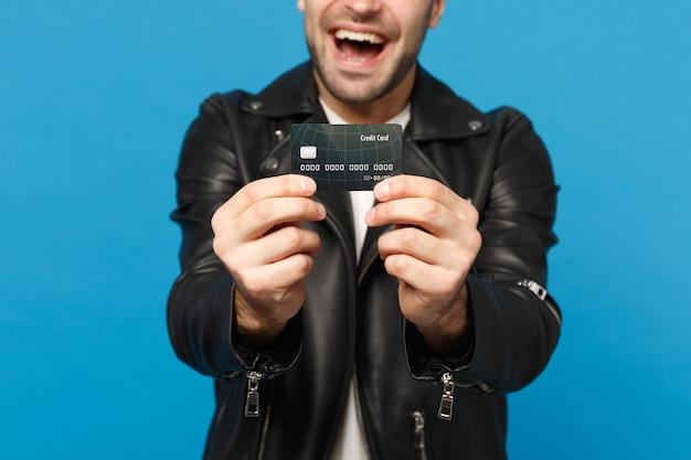 Bliska stylowy młody mężczyzna nieogolony w czarną skórzaną kurtkę biały t-shirt trzymać w ręku karty kredytowej banku na białym tle na tle niebieskiej ściany portret studio. koncepcja życia ludzi. makieta miejsca na kopię.