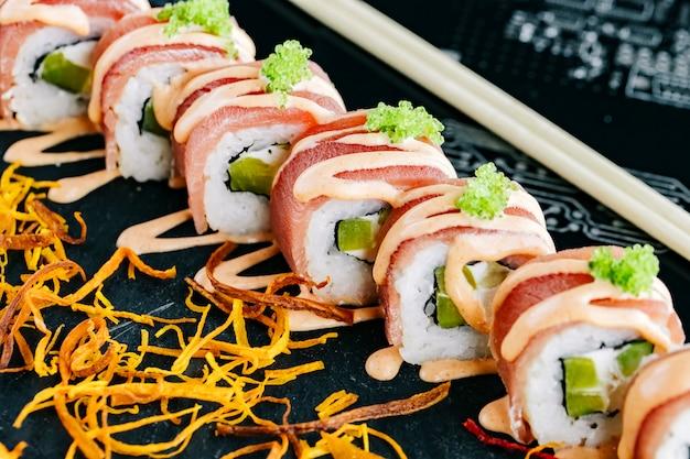 Bliska sushi z ogórkiem pokrytym tuńczykiem i przyozdobionym pikantnym sosem i zielonym tobiko