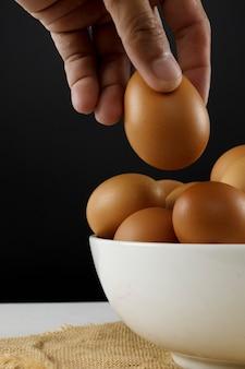 Bliska świeże jaja kurze na lnianym obrusie i białym stole z miejsca na kopię. mężczyzna ręka trzyma kurze jajko.