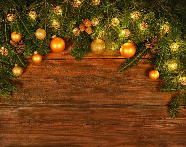 Bliska świeże zielone świerkowe lub sosnowe gałęzie choinki z dekoracją stożków, świateł, złotych, kulek i bombek, na tle ciemnobrązowych desek z miejsca na kopię