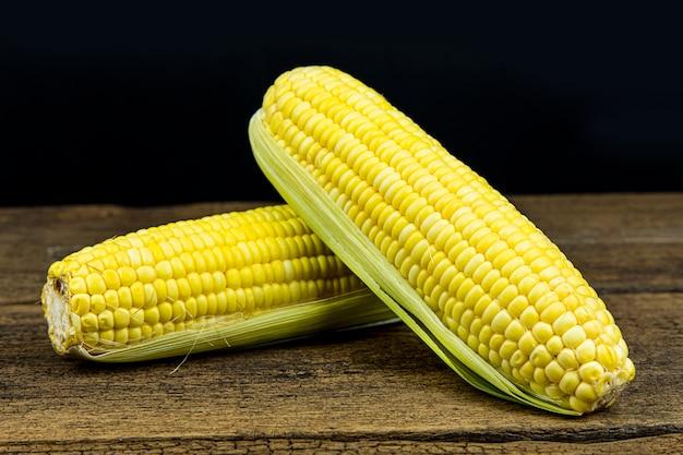 Bliska świeżej kukurydzy cukrowej na tle drewniany stół.