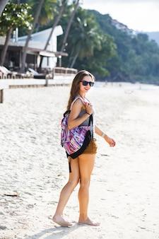 Bliska szczegóły młodej kobiety podróży na tropikalnej plaży, ciesz się wakacjami, spodenkami i plecakiem, zdrowe dopasowanie ciała. spacer i zwiedzanie tropikalnej wyspy.