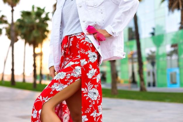 Bliska szczegóły mody, kobieta ubrana w seksowną spódnicę z nadrukiem maxi, białą luźną kurtkę i trzymająca neonowe okulary przeciwsłoneczne