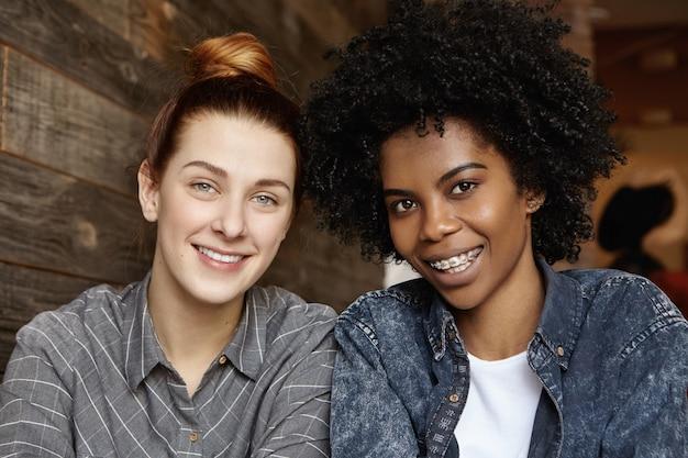 Bliska szczere ujęcie szczęśliwej kobiety z kręconymi włosami i szelkami, spędzającej wspaniały czas ze swoją rudowłosą dziewczyną