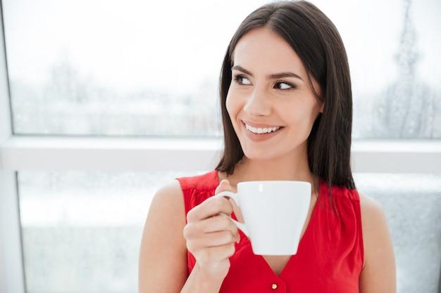 Bliska szczęśliwa kobieta w czerwonej koszuli stojąca w pobliżu okna z filiżanką kawy w biurze i odwracająca wzrok