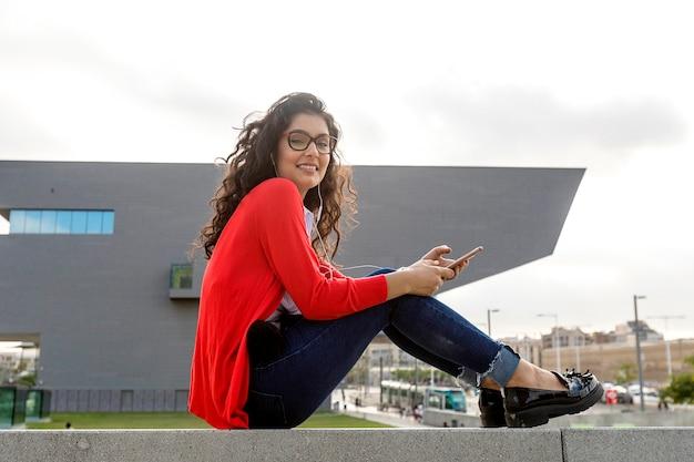 Bliska szczęśliwa młoda kobieta rozmawia z telefonem komórkowym poza miastem
