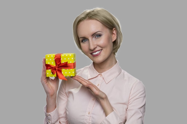 Bliska szczęśliwa uśmiechnięta kobieta pokazuje pudełko. dama atrakcyjny biznes trzymając małe pudełko na szarym tle.