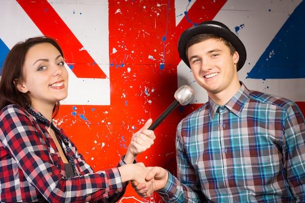 Bliska szczęśliwy młody mężczyzna i kobieta, z mikrofonem, w kraciaste koszule, ściskając ręce przed kamerą. uchwycony z przodu duży nadruk flagi brytyjskiej