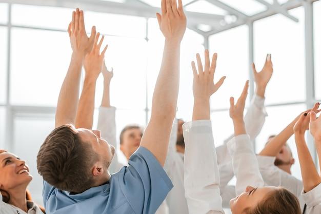 Bliska szczęśliwy zespół lekarzy z rękami do góry