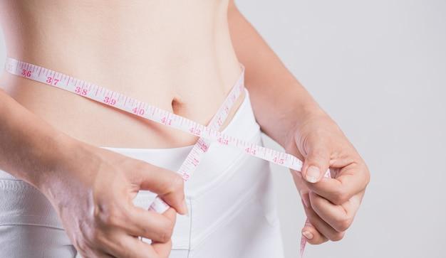 Bliska szczupła kobieta pomiaru jej cienką talię. opieka zdrowotna i koncepcja stylu życia diety kobiety, aby zmniejszyć brzuch i kształtować zdrowe mięśnie brzucha.