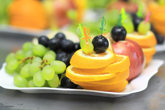 Bliska. tablica z winogronami i pomarańczami na rozmytym tle
