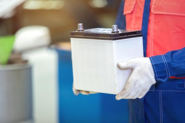 Bliska technik ręczny lub mechanik samochodowy trzymając akumulator samochodowy w centrum serwisowym naprawy samochodów.