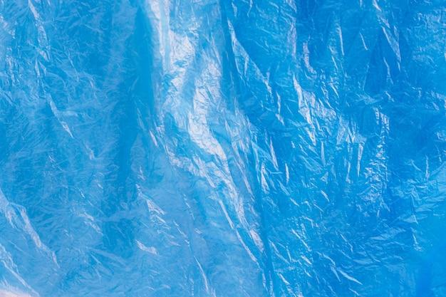 Bliska tekstura jasny niebieski plastikowy worek na śmieci. zmięty celofan. tło fioletowe folii polietylenowej. problem ekologii.