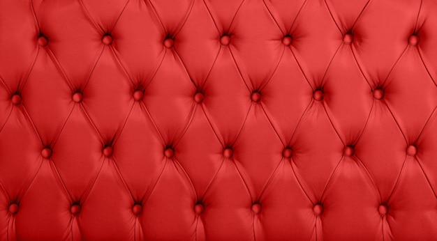 Bliska tekstura tła szkarłatnej czerwonej skóry capitone, miękka tapicerka meblowa w stylu retro chesterfield z głębokim wzorem rombów i guzikami