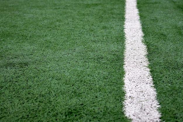 Bliska tekstury boiska piłkarskiego z białymi paskami, zieloną sztuczną powłoką.
