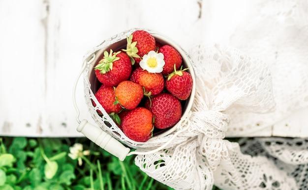 Bliska truskawki w wiadrze, lato we wsi, zbiory.