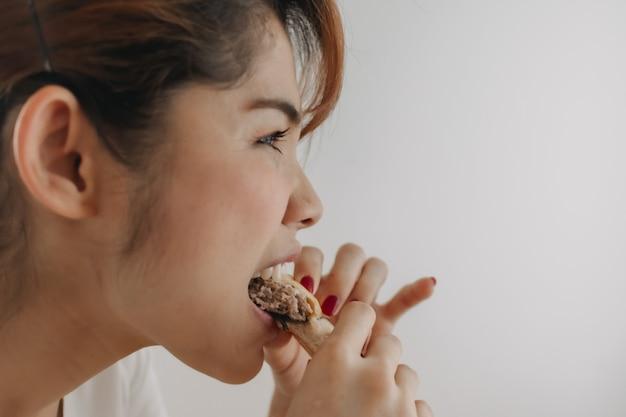 Bliska twarz kobiety gryzie kawałek chleba na białym tle