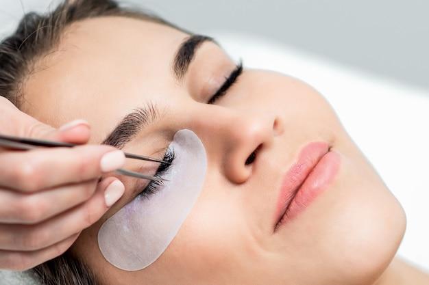 Bliska twarz kobiety otrzymującej procedurę przedłużania rzęs.