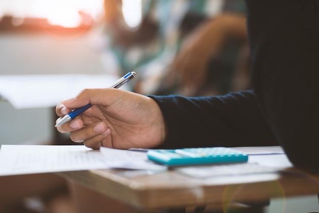 Bliska uczniowie piszący i czytający arkusze odpowiedzi na egzaminy ćwiczący w klasie szkoły ze stresem.