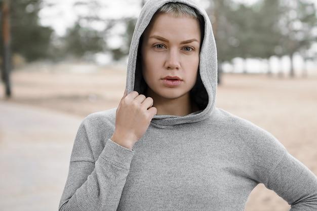 Bliska ujęcie dopasowanej pewnej siebie młodej kobiety wybierającej aktywny, zdrowy tryb życia, ćwiczącej na świeżym powietrzu, aby uzyskać idealną sylwetkę i schudnąć, pozując odizolowane w stylowej bluzie z kapturem, patrząc na kamery