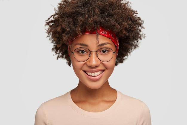 Bliska ujęcie przyjaźnie wyglądającej wesołej afrykańskiej kobiety z amrykanki z czułym wyrazem twarzy, przyjemnym uśmiechem, raduje się niesamowitą podróżą na letnie wakacje, nosi okrągłe okulary, modele w bieli