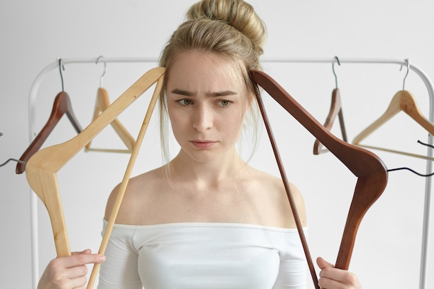 Bliska ujęcie zestresowanej pięknej młodej kobiety z otwartymi ramionami w białym blacie, trzymającej dwa puste stojaki na twarzy i marszczącej brwi, z zakłopotanym, zamyślonym spojrzeniem, myśląc, co włożyć do pracy